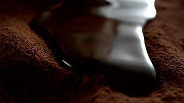 liquid chocolate flowing on cocoa powder. super slow motion - wine filmów i materiałów b-roll