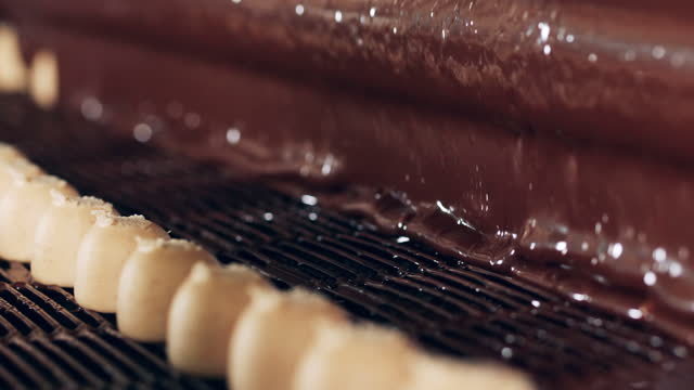 Liquid chocolate is covering fudge sweets during transportation video