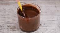 istock Liquid dark chocolate in bowl. Female hand mixing melted dark chocolate with spatula 1258108606