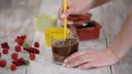 istock Liquid dark chocolate in bowl. Female hand mixing melted dark chocolate with spatula 1265488884