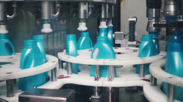 Liquid detergent on automated production line. Clip. Automated production line of washing fluid. Machinery for bottling video