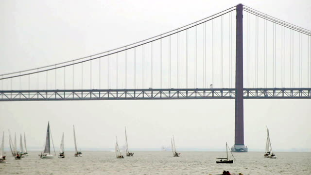Lisbon bridge and sailboats Lisbon bridge and sailboats  ponte 25 de abril stock videos & royalty-free footage