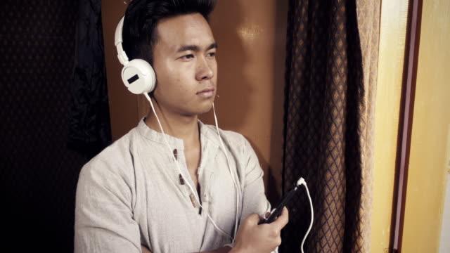 ヘッドフォンでポッド キャストを聞いています。 - ネパール人点の映像素材/bロール