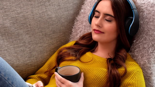 Listening to music on headphones relaxing with coffee on sofa. Dolly shot of a beautiful young woman lying on a sofa listening to music on headphones sometimes closing her eyes as she relaxes while holding a coffee. listening stock videos & royalty-free footage