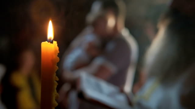Lit candle on background of father with child ready for church ritual video