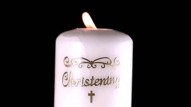 Lit christening candle flickering video
