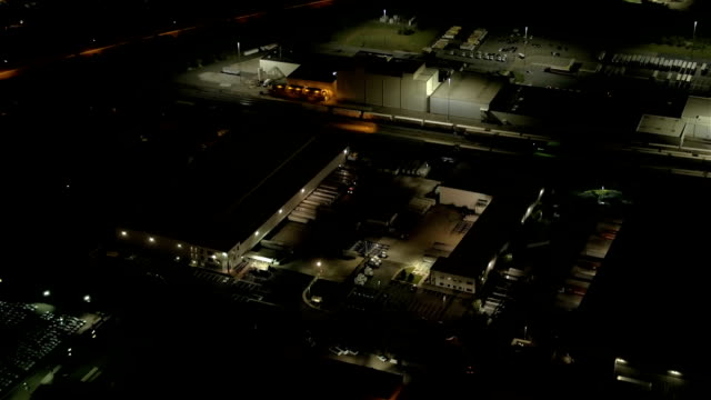 AERIAL: Lit logistic center in commercial zone with access to highway at night video