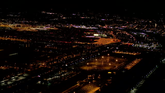 AERIAL: Lit up with lights warehouse, logistics and distribution center at night video