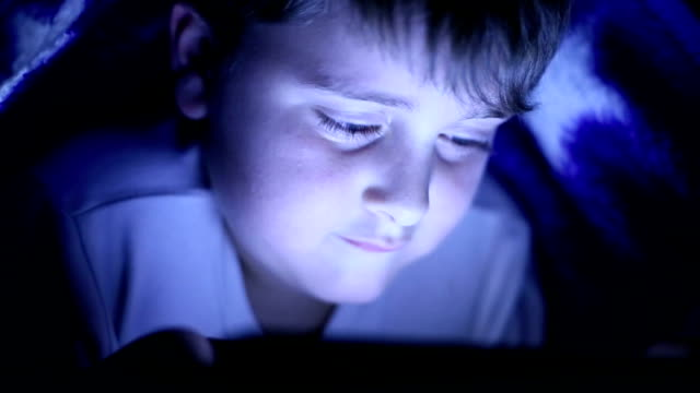 Litlle kid playing with tablet under cover video