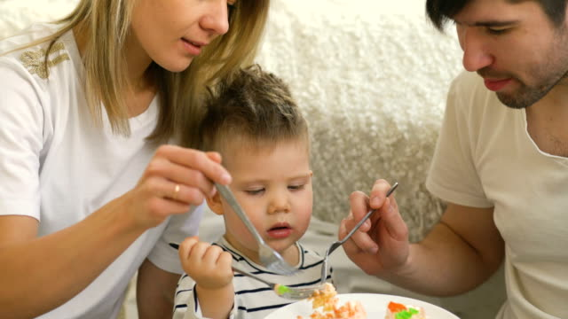 Little adorable boy celebrating his birthday feeding his father and mother with cake – Video