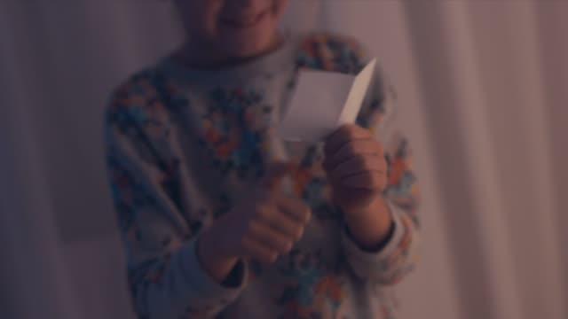 vidéos et rushes de cu petite fille adorable ouvre l'enveloppe quotidienne à partir d'un calendrier de l'avent noël vacances saison à son appartement - calendrier de l'avent