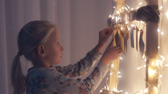 CU Little adorable girl unties the rope to get a daily envelope from a hand made advent calendar at her apartment video