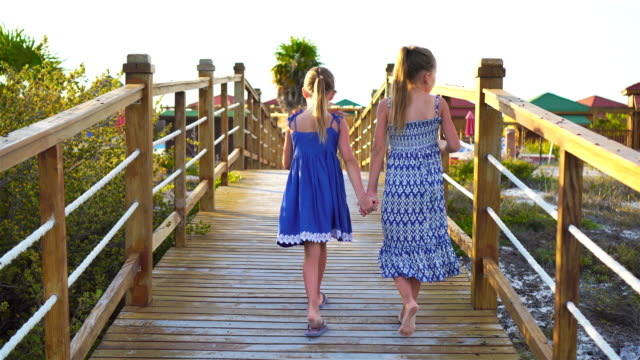 Little adorable girls on a wooden bridge on their way to a white tropical beach and turquoise ocean