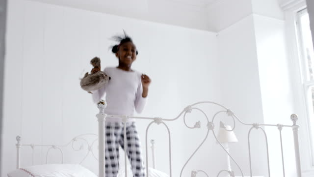 Little african girl jumping on the bed video
