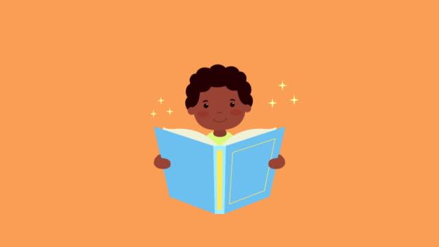 lilla afro pojke läsning bok - digital reading child bildbanksvideor och videomaterial från bakom kulisserna