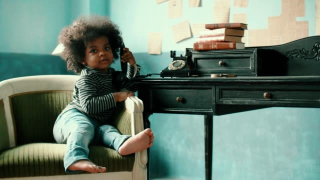 Little afro girl(2-3 years) talking on rotary phone at home Handheld shot of african-american girl(2-3 years) sitting on vintage chair and using rotary phone, 4K Resolution telephone receiver stock videos & royalty-free footage