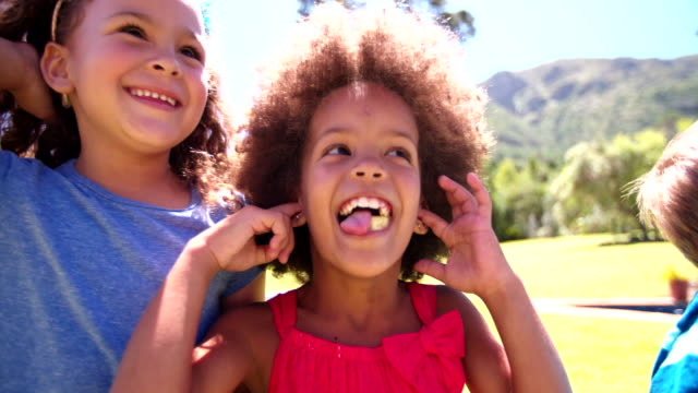 Little Afro girl with friends smiling in summer sunlight video