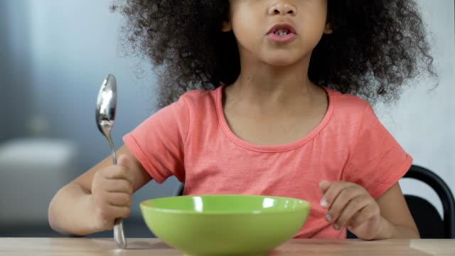маленькая афро-американская девушка сидит за столом с ложкой и просит ужин - голодный стоковые видео и кадры b-roll