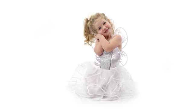 Little angel girl dressed in white angel clothes on white video