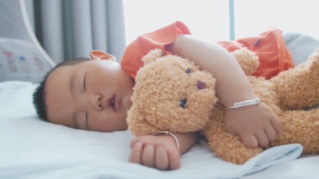 vídeos de stock e filmes b-roll de little asian baby boy sleeping with teddy bear - teddy bear