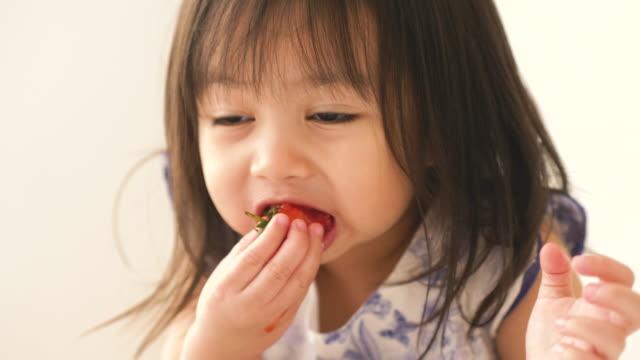 vídeos de stock, filmes e b-roll de menina asiática é comer morango no quarto dela - comida feita em casa