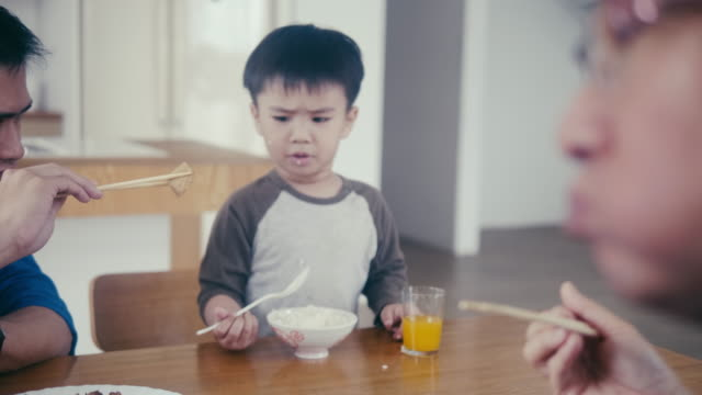 Little asian boy eats rice and drink juice