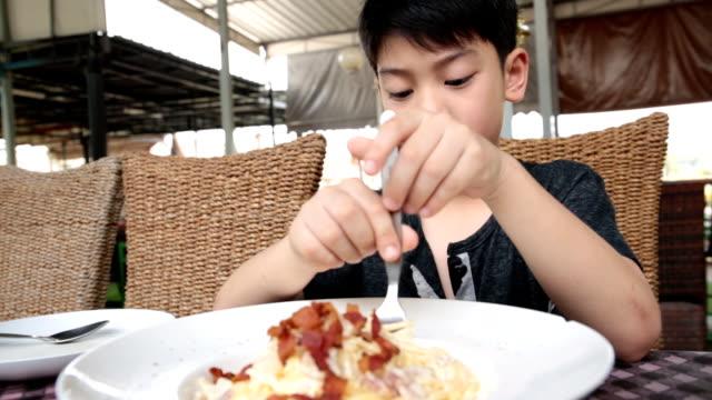 vídeos y material grabado en eventos de stock de little asian niño comiendo pasta en el restaurante. - gran inauguración
