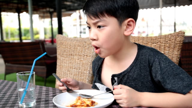 little asian child eating pizza at restaurant . - grand opening stock videos and b-roll footage