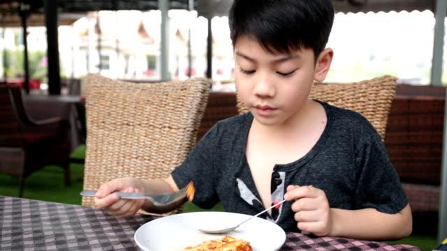 vídeos y material grabado en eventos de stock de little asian niño comiendo una pizza en el restaurante. - gran inauguración
