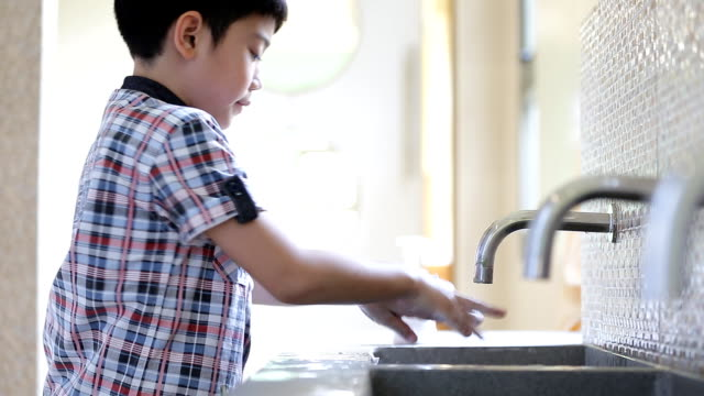 Little asian child washing hands . video
