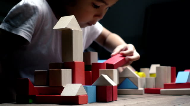 Little asian girl and boy playing wood blocks together. slow motion shot. video