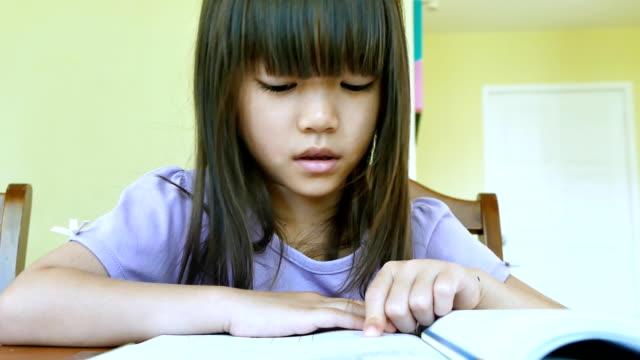 小さなアジアの女の子が宿題をし ビデオ