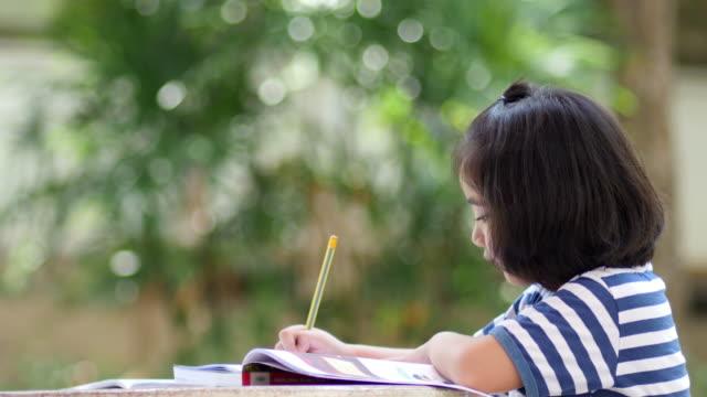 宿題小さなアジアの女の子を行う ビデオ