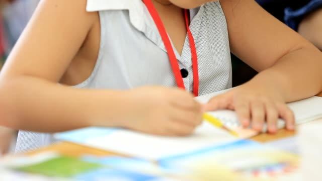小さなアジアの女の子の画像に描画テーブル - 勉強する点の映像素材/bロール