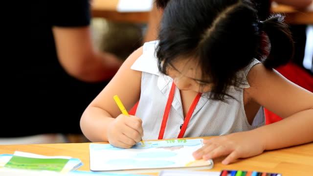 小さなアジアの女の子の画像に描画テーブル ビデオ