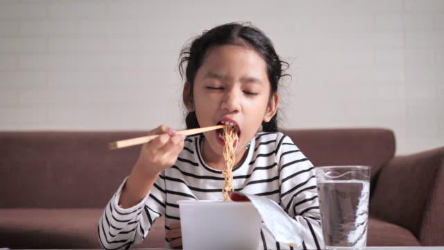 幸せで熱くてスパイシーなインスタントラーメンを食べる小さなアジアの女の子は、被写界深度の焦点浅い選択 - 不健康な食事点の映像素材/bロール