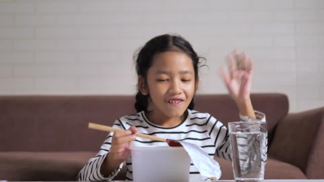 幸せでインスタントラーメンを食べる小さなアジアの女の子は、被写界深度の浅い焦点を選択します - 不健康な食事点の映像素材/bロール
