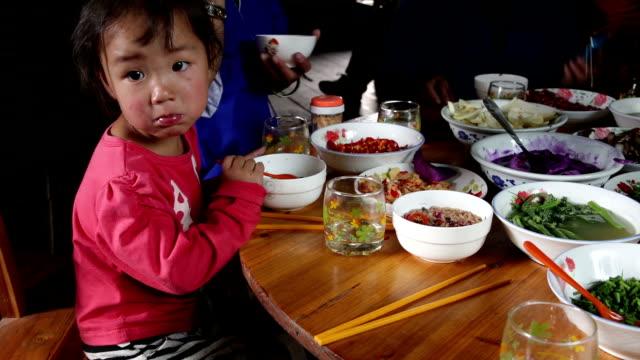 Wenig asiatische Mädchen isst traditionelle Speisen – Video