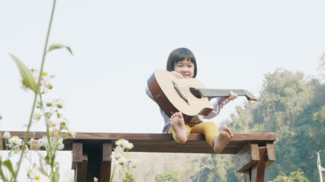 Little asian girl is playing guitar with relax and leisure at the seating beside the garden Little asian girl is playing guitar with relax and leisure at the seating beside the garden young singles stock videos & royalty-free footage