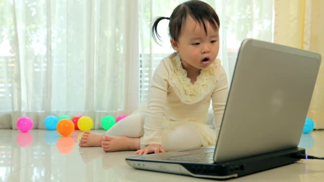 Little asian girl play laptop in home video
