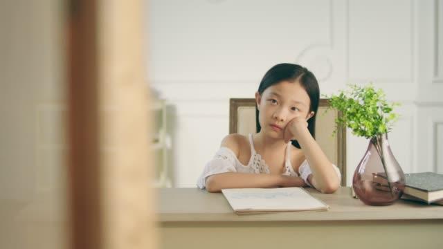 küçük asyalı kız masa düşünme oturuyor - orta plan plan türleri stok videoları ve detay görüntü çekimi