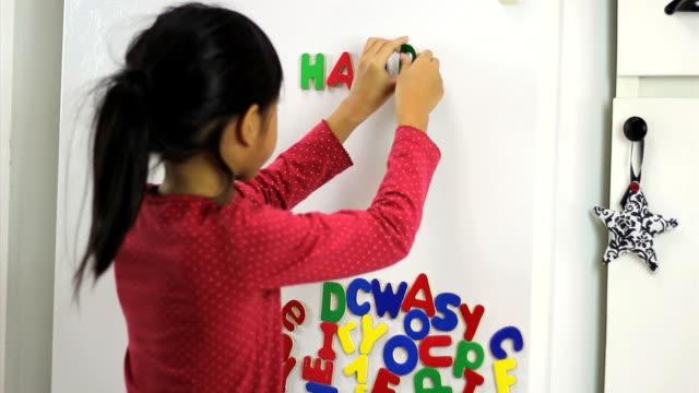 little asian girl spelling happy birthday on fridge - stavning bildbanksvideor och videomaterial från bakom kulisserna