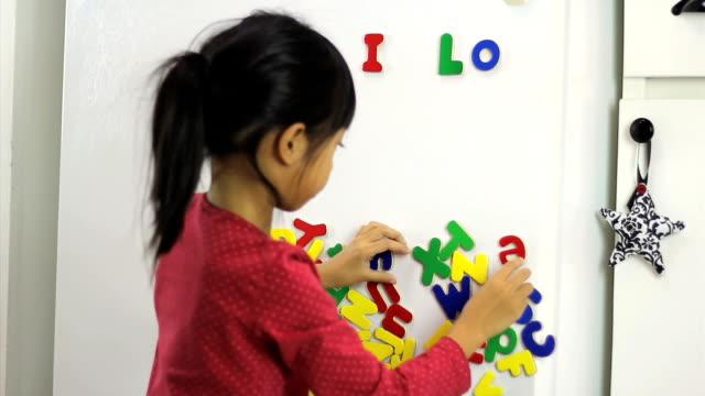 Pequena menina asiática ortografia Adoro PAI na geladeira - vídeo