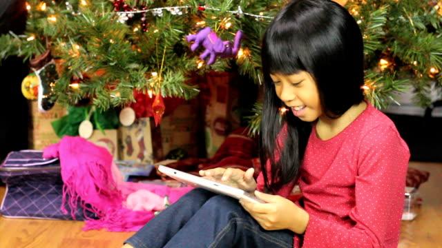 Little Asian Girl Using Tablet Beside Christmas Tree video