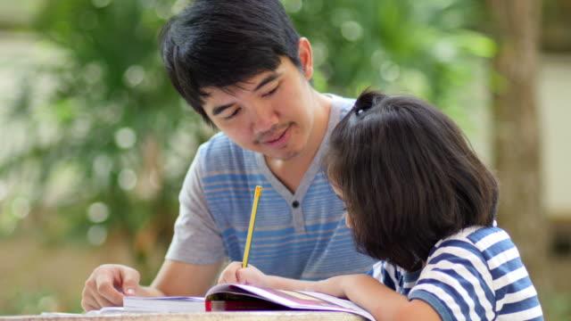 小さなアジアの女の子、父親て、テーブルに宿題 - 託児施設点の映像素材/bロール