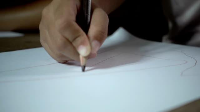 Little asian girl writing on desk in dark room, slow motion shot. video