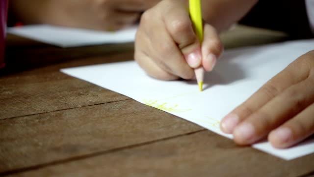 liten asiatisk tjej som skriver på skrivbord i mörkt rum, slowmotion sköt. - linjerat papper bakgrund bildbanksvideor och videomaterial från bakom kulisserna