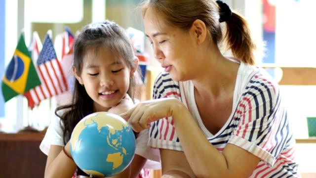 4 k 小さなアジア学生、教師、日本語教育を聴きながらグローブを見て - 託児施設点の映像素材/bロール