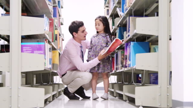 Little Asian students and teacher reading book in library. video