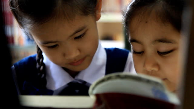 mały azjatyckich studentów na sobie stroje i czytanie książki w bibliotece - uniform filmów i materiałów b-roll